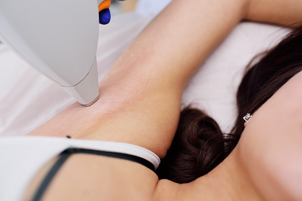 a young woman in a modern cosmetology clinic on the procedure of laser hair removal of the armpit area