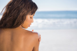 Relaxed woman on the beach applying sun cream on her shoulder