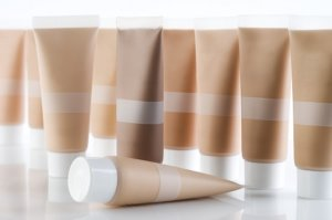 Many cosmetic tubes with creams standing on reflective background