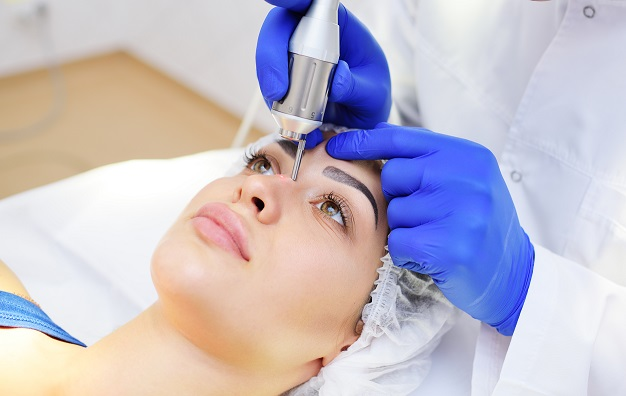the surgeon beautician removes pigmentation and vascular nets on the skin of the patient-a beautiful young woman neodymium laser. Laser cosmetology