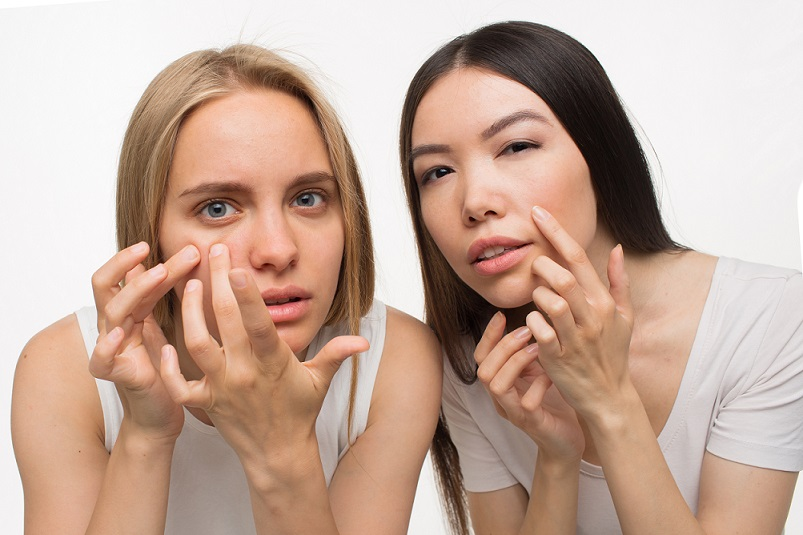 Blonde and brunette young women look close to camera. They hold fingers on cheeks. They touch pimples on face. Isolated on white background