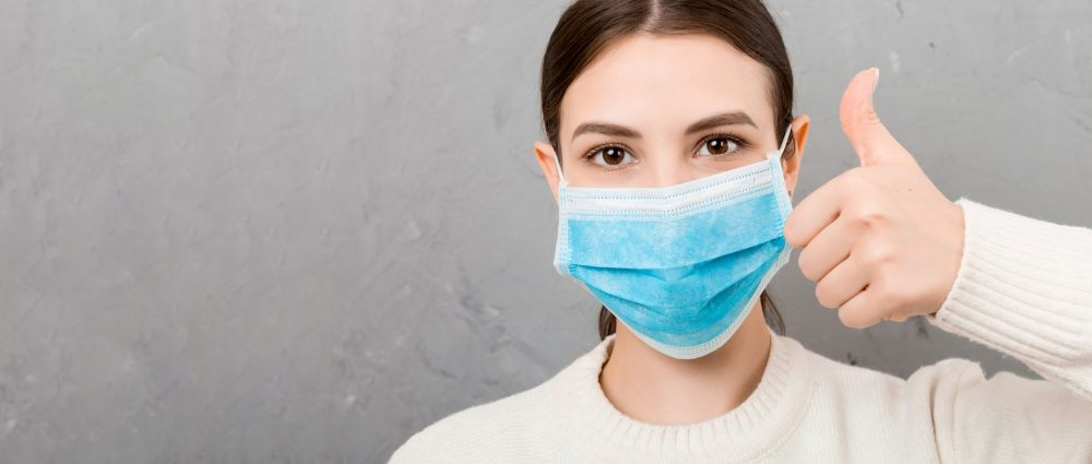 Portrait of young woman wearing medical mask at gray cement background. Person is happy because she is finally healthy. Protect your health. Coronavirus concept.