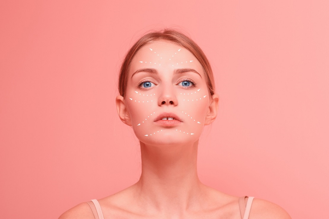 Young beautiful female close up facial portrait with arrows on her face on pink background