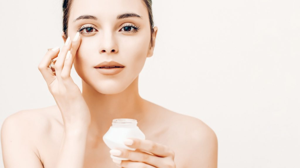 Natural beauty portrait of young woman applying cream on her face