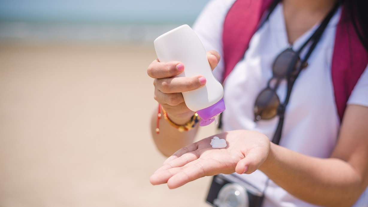 Female hands with sunscreen at the beach. Skin care concep