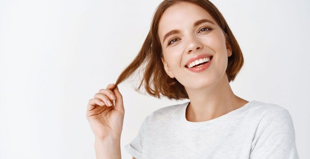 Close-up portrait of tender girl with short hair, smiling white teeth and looking happy, playing with haircut, standing against white background.